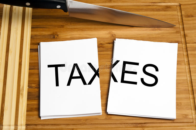 Knife cut paper with taxes. Word royalty free stock images