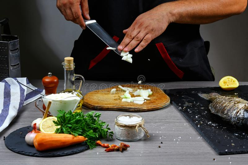 Knife cutting onion. Sliced vegetables on wooden board. Ingredient for Stuffed Fish with Vegetables.  stock photos