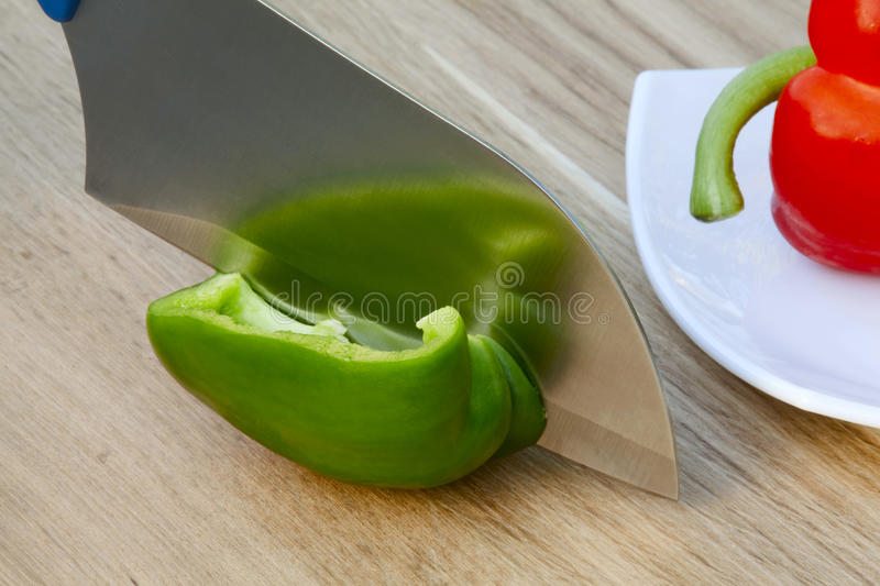 Knife cutting the pepper stock image