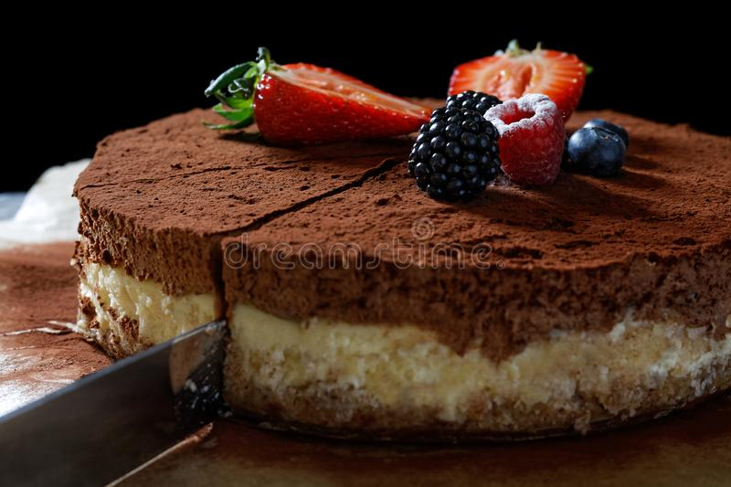 A knife cutting a slice of homemade cheesecake on baking paper with cocoa and fruit topping royalty free stock images