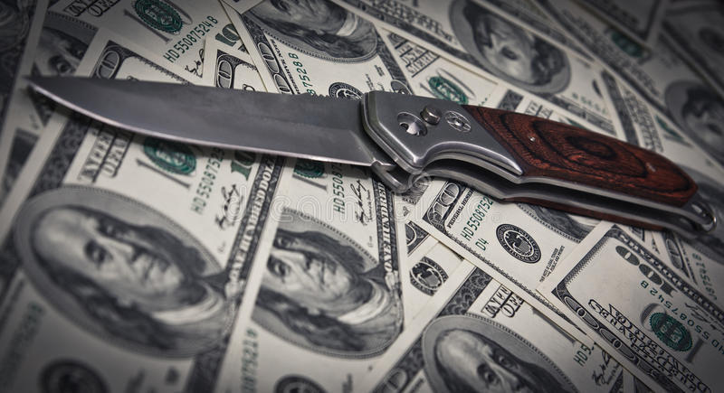 Knife and dollars. Danger. Dramatic spotlight image royalty free stock images