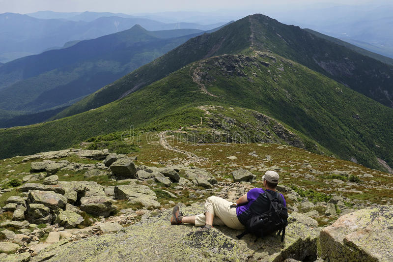 The Knife Edge on Lafayette Ridge, Appalachian Trail. A hiker takes a rest on Mount Lafayette in New Hampshire's White Mountains. This knife-edge section of the royalty free stock photography