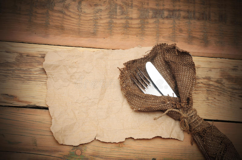 Knife and fork. In rough old sacking on blank paper over wood stock photography