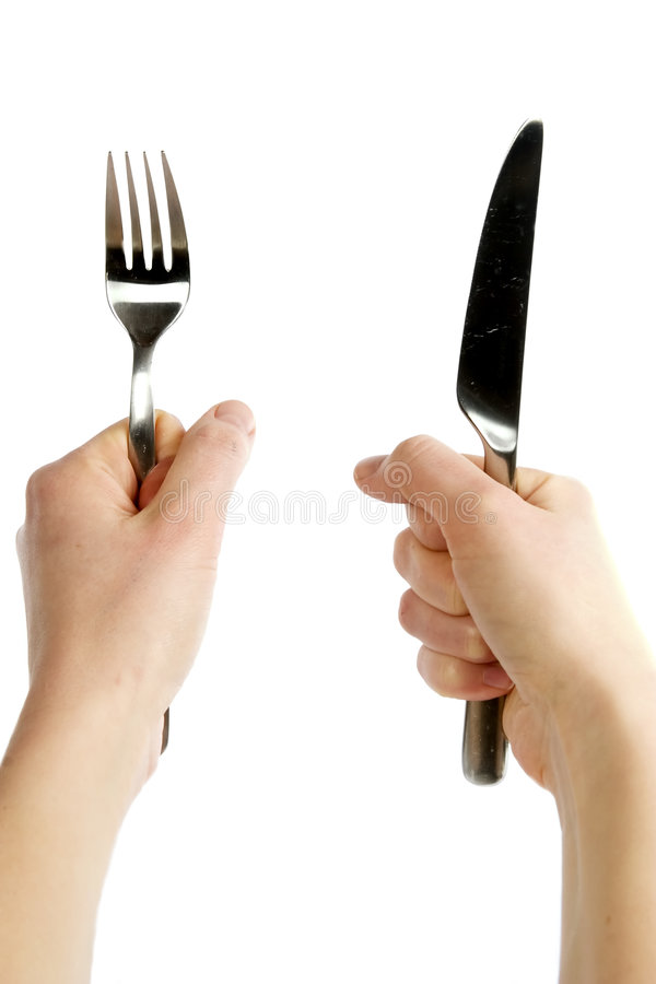 Knife and Fork. A knife and fork being held by womans hands. Isolated on white royalty free stock photo