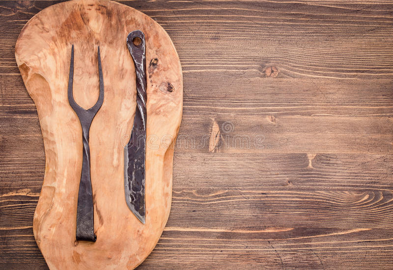 Knife and fork on cutting board from left of table royalty free stock photo