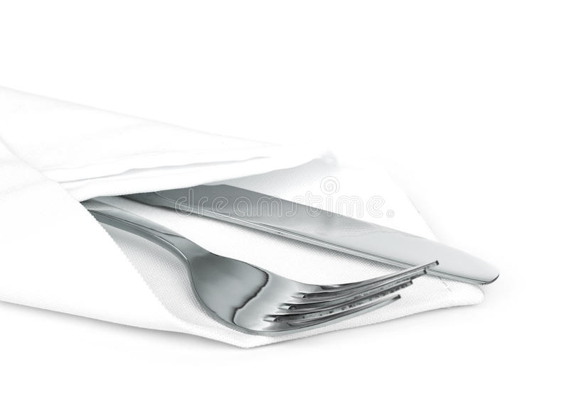 Knife and fork with linen serviette. On white stock photo