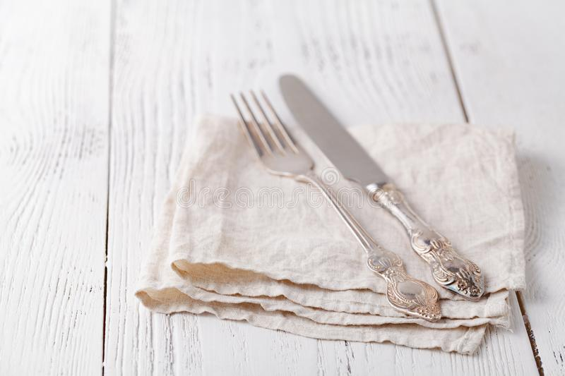 Knife, fork with linen serviette on the white background royalty free stock photos