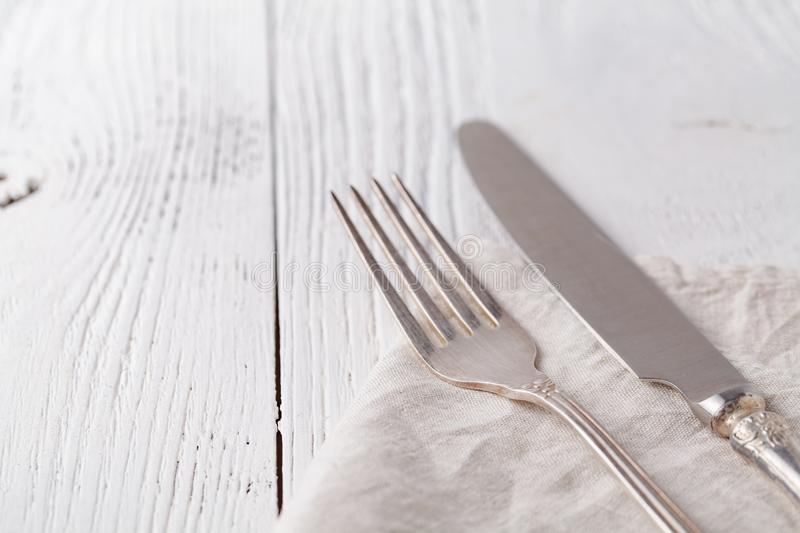 Knife, fork with linen serviette on the white background royalty free stock images