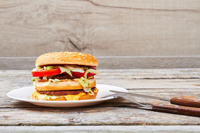 Knife and fork near burger. Plate with hamburger. How to cook a hamburger stock photo