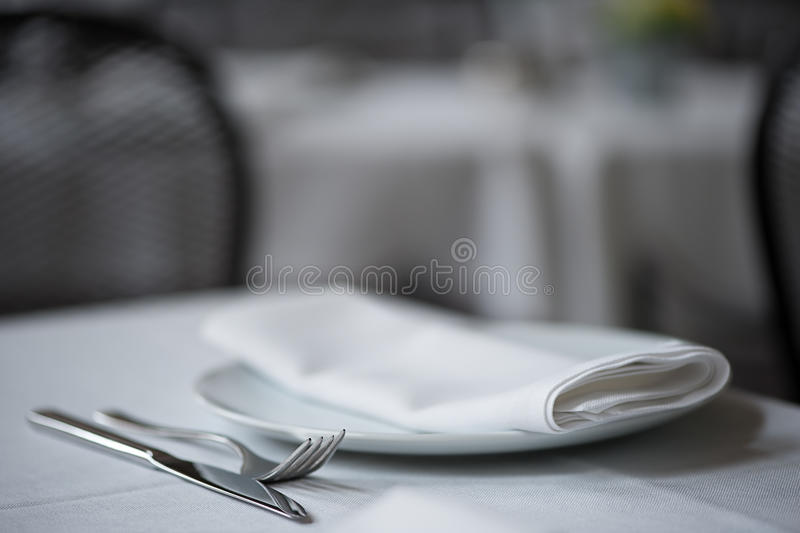 Knife, fork, plate and folded napkin upon white table cloth. Shallow depth of field close up of knife, fork, plate and folded napkin laid upon white table cloth stock photography