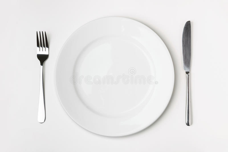 Knife, Fork and plate on table. stock photography