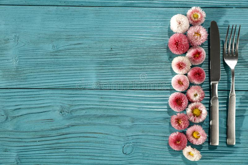 Knife and fork with small flowers on turquoise wooden board background. Knife and fork with small flowers on blue turquoise wooden board background Some empty royalty free stock image