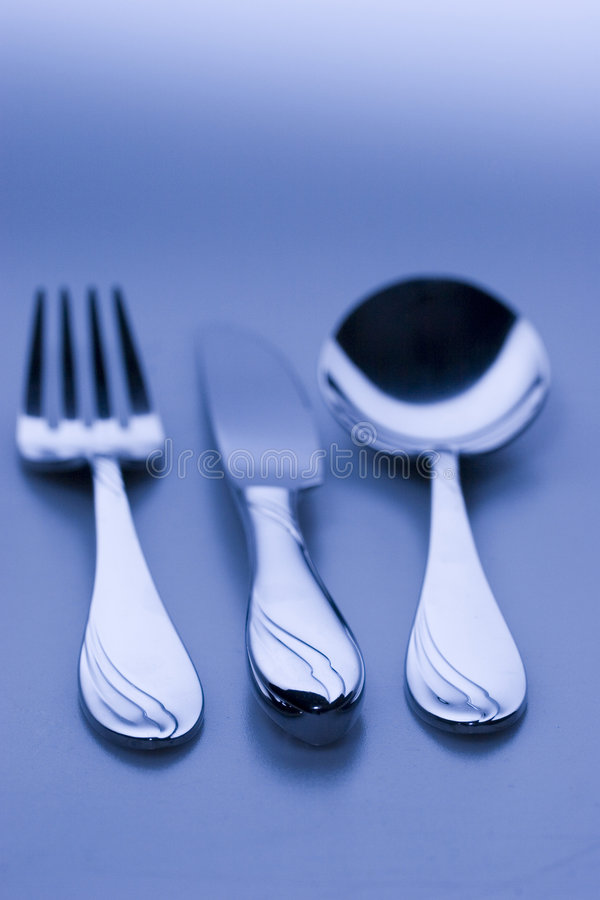 Knife, fork, spoon blue colored. Knife, fork, spoon with focus on grips in blue lighting stock images