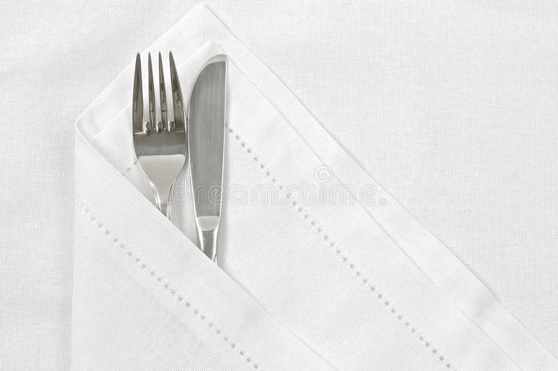 Knife and fork with white linen serviette. And space for text stock photography