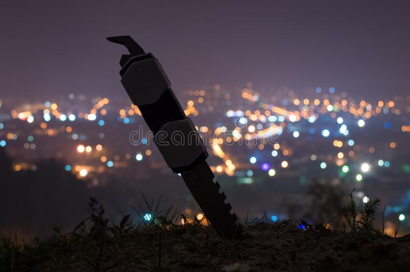 A knife in front of a city royalty free stock photography