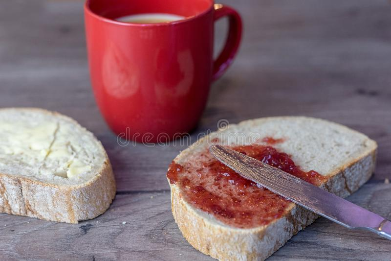 Knife lays on top of a slice of bread that has jam spread over it on top of a wooden table royalty free stock images