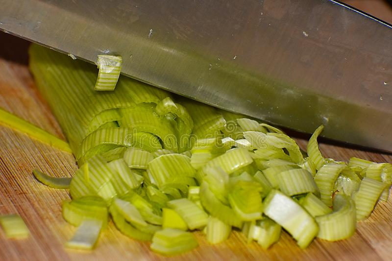 A knife on the leek. Slipping the leek with a knife, we prepare a delicious dinner stock photos