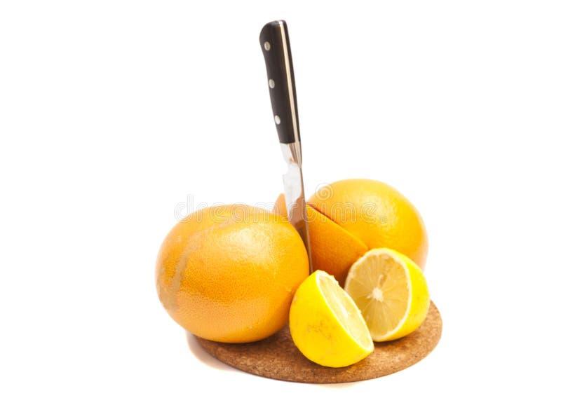Knife with orange and lemons. On white background royalty free stock image