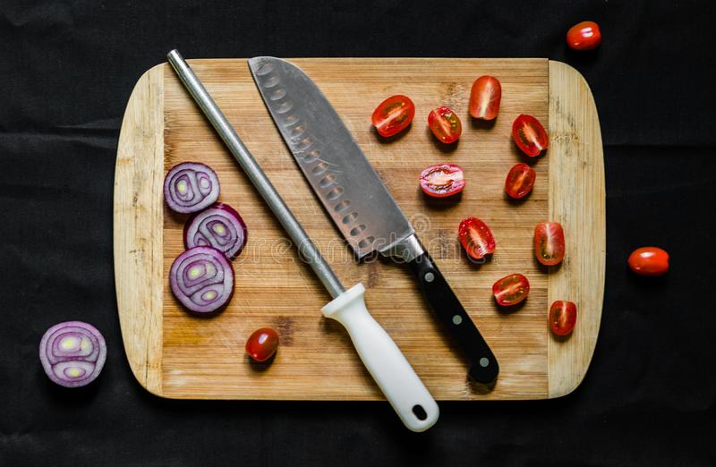 A knife sharpener and a chef knife on a cutting board with vegetables. Knife sharpener and a chef knife on a cutting board with vegetables stock image