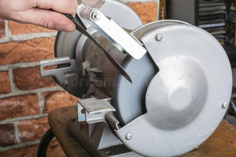 Knife sharpener and hand with blade on wooden table, closeup royalty free stock image