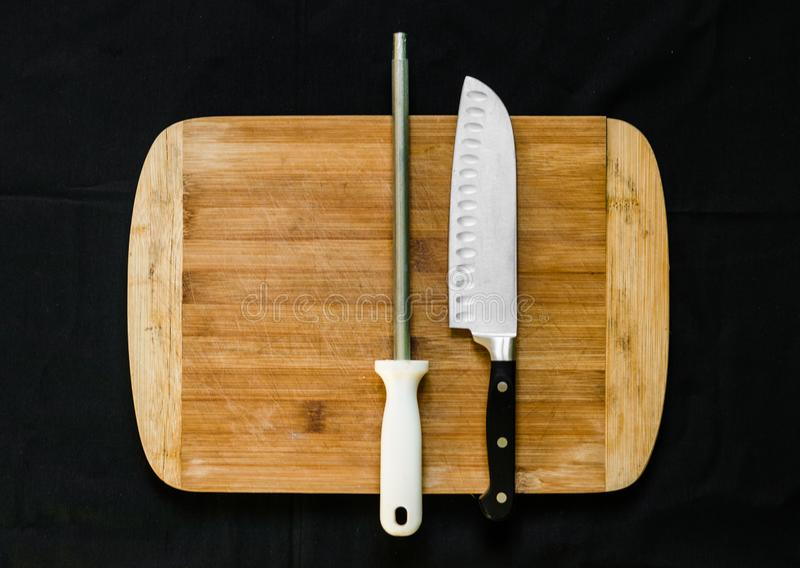 A knife sharpener, or honing steel, and a chef knife on a cutting board. Knife sharpener, or honing steel, and a chef knife on a cutting board stock photography
