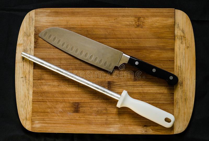 A knife sharpener, or honing steel, and a chef knife on a cutting board. Knife sharpener, or honing steel, and a chef knife on a cutting board stock photo