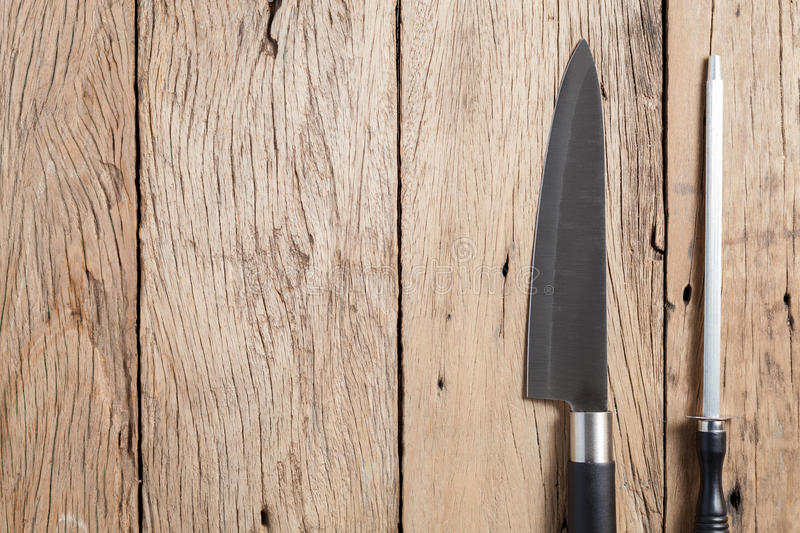 Knife and Sharpener on old wooden table background. Knife and Sharpener on old wooden table background stock photography