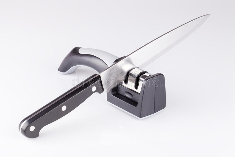 Knife and sharpener. Knife and knife sharpener on a white surface. Kitchen tools isolated on white background royalty free stock image