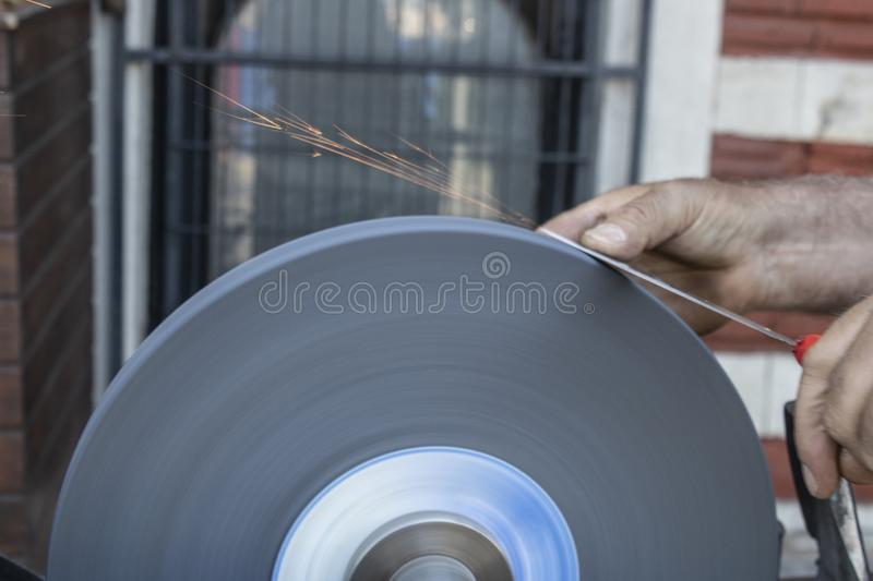 Knife sharpening hand and sanding machine close-up royalty free stock photos