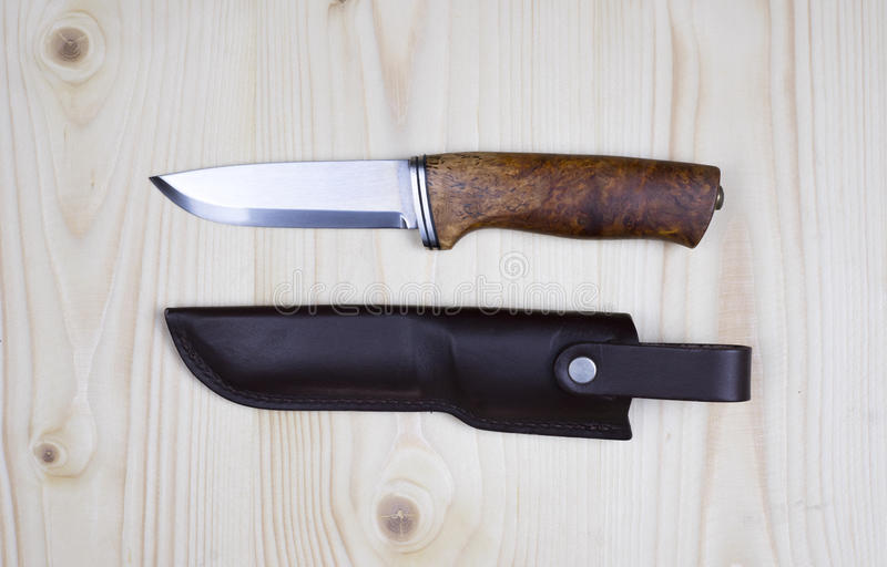 Knife and sheath on flat pine wood. stock images