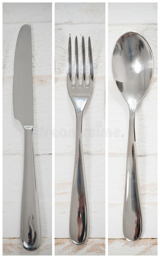 Knife, spoon and fork on a white wooden table. A knife, spoon and fork on a white wooden table stock photography