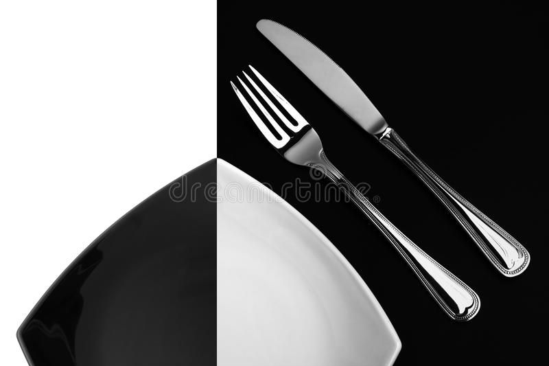 Knife, square white plate, fork on black top view. Knife, square white or black plate and fork on black or white background stock photography