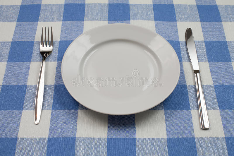 Download Knife, White Plate And Fork On Blue Tablecloth Stock Photography - Image: 16704122