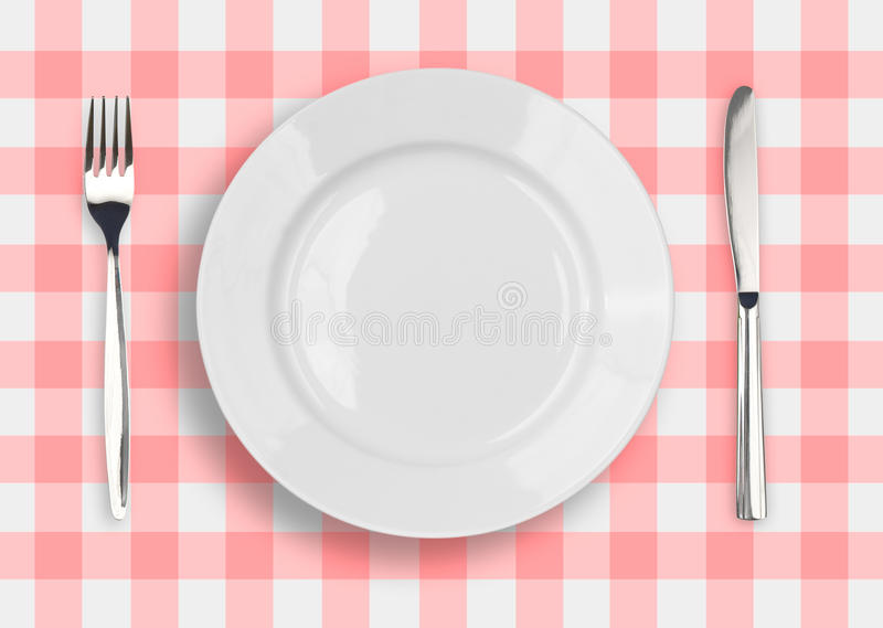 Knife, white plate and fork on checked top view. Knife, white plate and fork on blue checked tablecloth royalty free stock photos