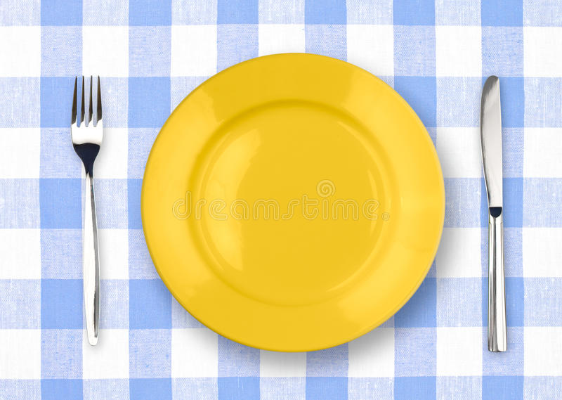 Knife, Yellow Plate And Fork On Checked Tablecloth Stock Photography