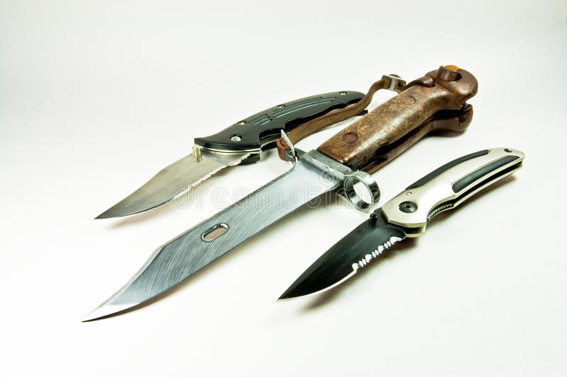 Knifes and old army bayonet. Here we have 2 folding knives alongside an old army bayonet. You can see the big differences in size, but all three blades are stock photography