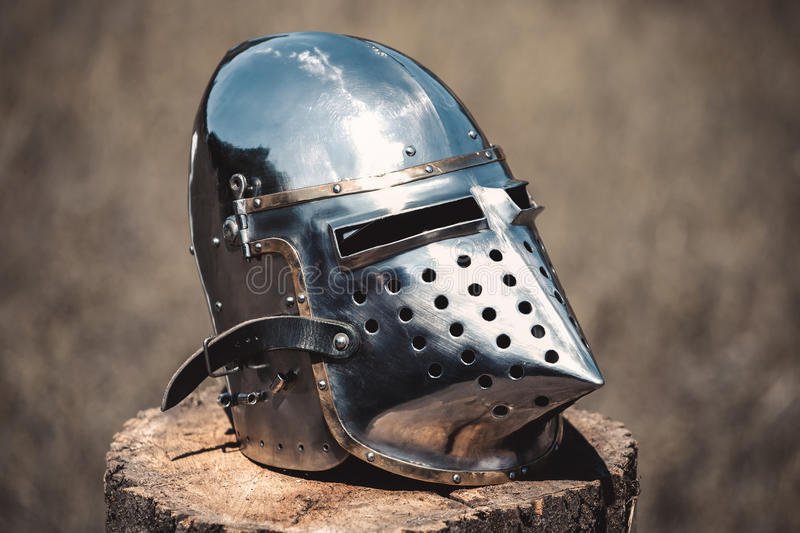 Knight, a brilliant helmet standing on a wooden stump royalty free stock image