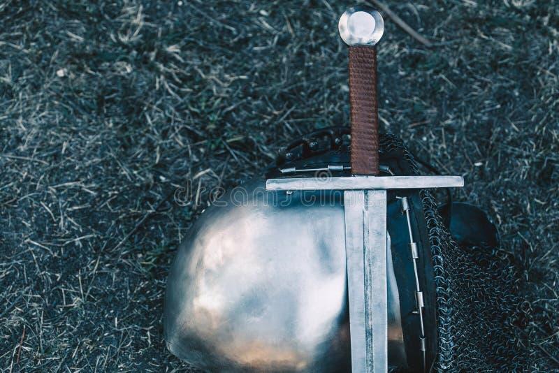 Knight& x27; capacete de s e metal brilhante que encontram-se na terra, pôs uma espada de aço velha com punho de couro foto de stock royalty free