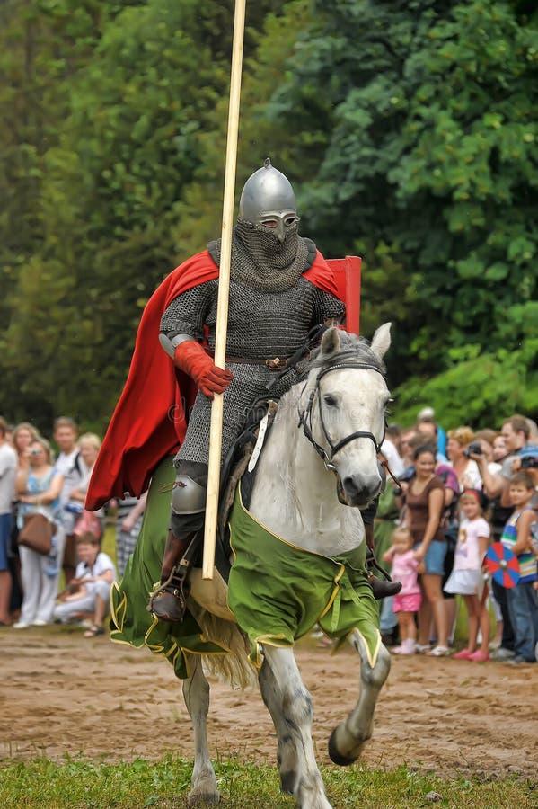 Knight el casco y el escudo a caballo con la justa imagenes de archivo