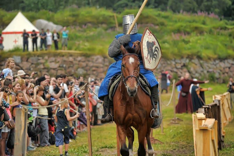 Knight el casco y el escudo a caballo con la justa imagen de archivo