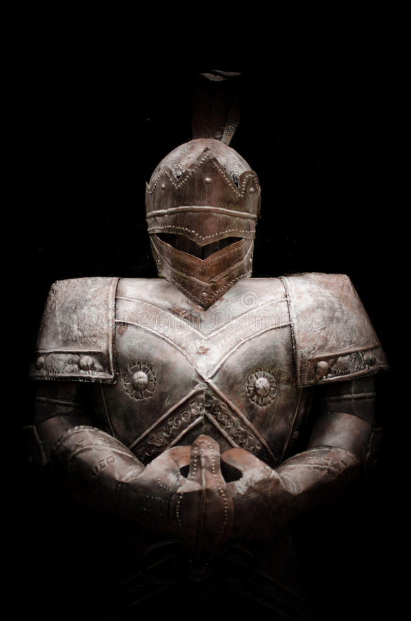 Knight holding sword in darkness. Knight holding sword with metal armor facing forward in darkness royalty free stock photo