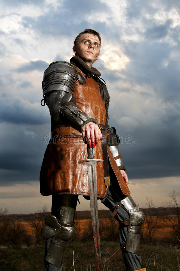 Knight holding sword on a sky background stock photography
