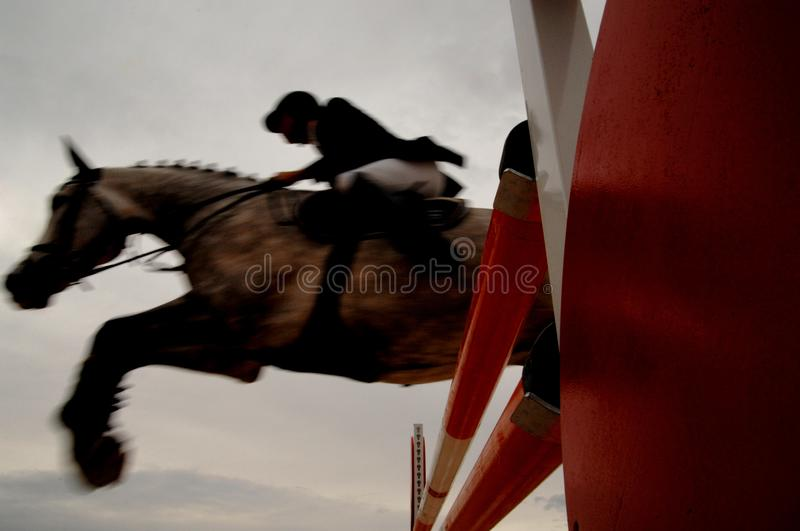 Knight jumps obstacle with horse. Overcome difficulties concept royalty free stock photo