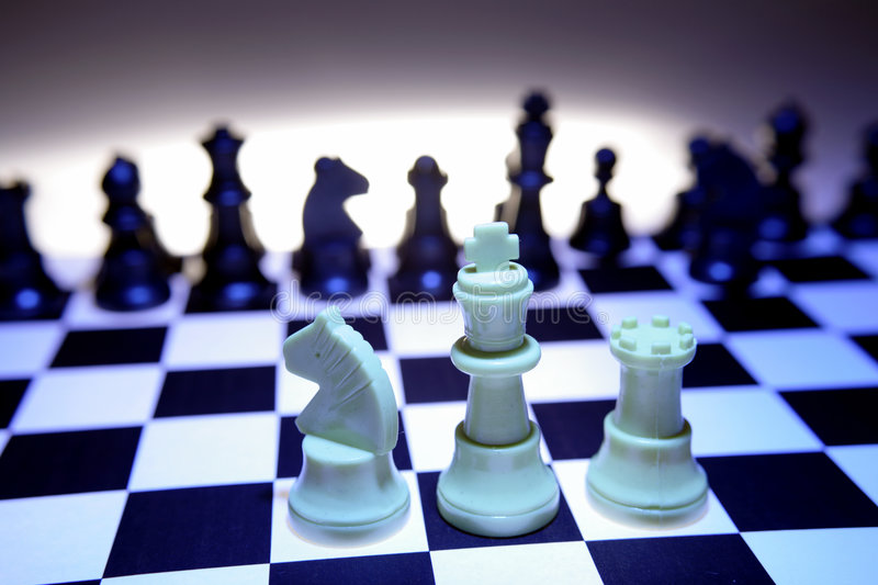 Knight king and castle chess. White knight, king and castle chess pieces facing off against black pieces across the chessboard stock images