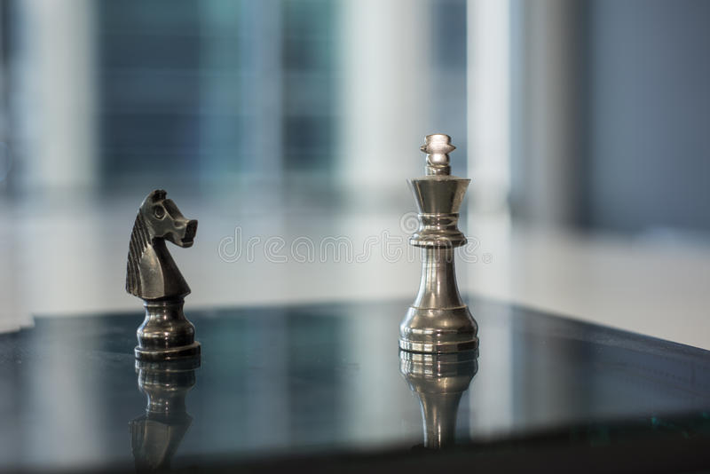 Knight and King. Chess pieces, knight and King on a reflective surface stock photo