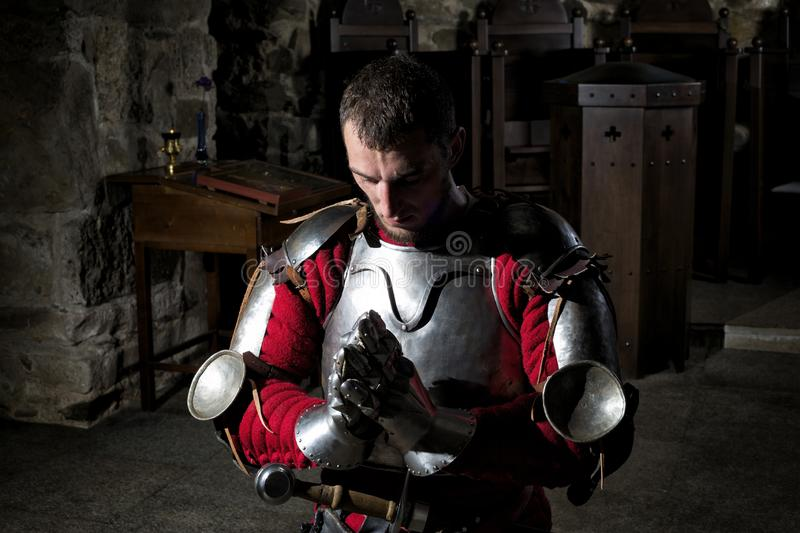 Knight Kneeling On His Knees With Bowed Head And Praying Hands stock photography