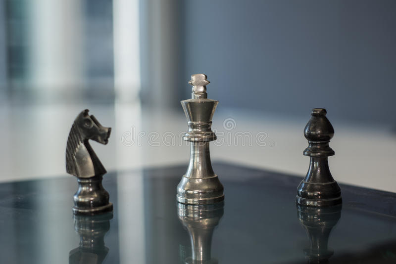 Knight, Pawn and King. Chess pieces, knight, pawn and King on a reflective surface stock photo