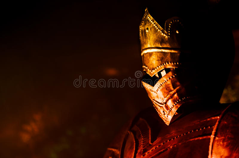 Knight profile with fire reflections. Knight with metal armor side view with reflecting fire in the dark stock image