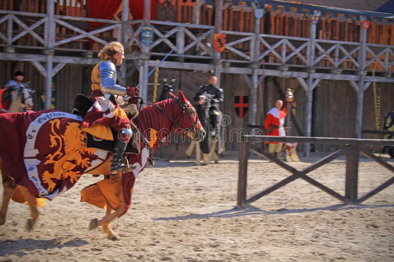 A Knight riding his horse. Knight`s games started. Knight rides and horse. He`s wearing an armor and holding a sword. It`s happening at an arena. The knight is stock photography