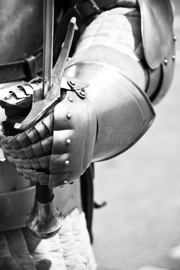 Knight's hands holding a sword royalty free stock photography